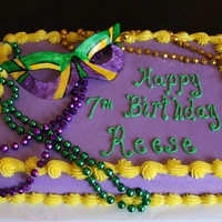 Mardi Gras Birthday Cake 9x13 yellow butter cake with buttercream frosting. Mask is gumpaste, hand painted with Americolor food color mixed with vodka and gold...