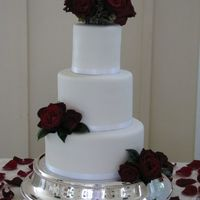 Red Roses Fondant covered cakes, satin ribbon and real roses.