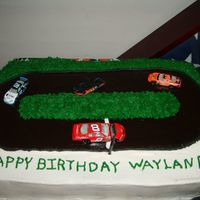 Race Track i made this for sons 11th birthday. The cake is a 9x13 covered is buttercream bc grass and chocolate MMF race track