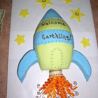 "Welcome Earthling Rocketship Marshmallow fondant icing on rocketship and buttercream ""exhaust""."