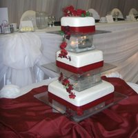 Wedding   cake is covered in BC with MMF, red ribbon around each tier, made plastic stands and used glass window cubes with battery lights inside.