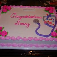 Nurse Graduation White cake with buttercream frosting and flowers. Needle, pills, band-aid and stethoscope are made of mmf.