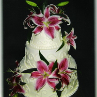 Stargazer Cake vanilla, chocolate and strawberry layers, vanilla frosting, stargazer lilies, and icing desings