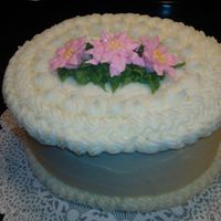 December Bridal Shower Oval shaped orange soda cake with twinkie filling and crusting cream cheese with orange flavor. Pink poinsettias are royal icing.