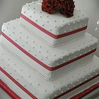 Red Theme Wedding Cake vanilla and chocolate cake. marshmallowcreme buttercreme frosting. strawberry filling. white rolled fondant. gumpaste roses and pearls.