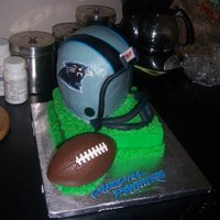 Carolina Panthers Helmet  Made with, 2 six inchs rounds, 1 half sports ball pan, sitting on an 8X2 square cake...iced in butter cream, with fondant details. Football...