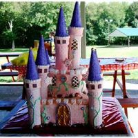 "Pink Castle Cake  THIS IS A SQUARE 10 CAKE WITH A 6"" ON TOP.THE COLUMS ARE ROYAL ICING DIPPED ICECREAM CONESW/CAKE SPARKLES. THE DOORS AND WINDOWS ARE..."