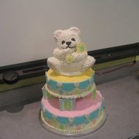 Teddy Bear Baby Shower Cake 2-Tiered Cake with 3D Bear cake on top. Iced in buttercream with fondant accents. Re-created from the Wilton Tiered Cakes book.