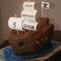Pirate Ship Chocolate cake filled with chocolate ganache and iced in chocolate buttercream. Sails are gumpaste, and Tootsie Rolls were used for the...