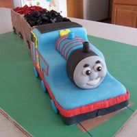 Thomas The Tank Engine For my son's 3rd birthday. Started with a 12x18 sheet cake & made Thomas & the 2 cars behind him. Covered in MMF with piped...