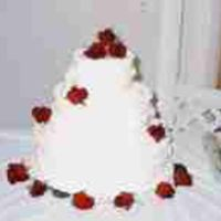 3 Tier All White Wedding Cake With Real Roses This is a 3 tier stacked French Vanilla wedding cake with white buttercream roses on the sides of the cake and fresh red roses added.