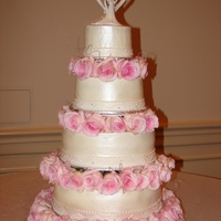 Four Tier Pink Rose Wedding Cake Four tier all buttercream with fondant ribbon and fresh roses