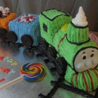 Percy Train Cake Chocolate & Vanilla cake with bc icing. Face of train is fondant/gumpaste and train tracks are black licorice. TFL. :-)