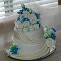 White Roses With Blue Daisies This is my very first paid wedding cake.