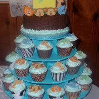Noah's Ark Cupcake Tower Top is an oval cake iced in chocolate fudge frosting. 30 cupcakes, all iced in buttercream. Decorations I made out of fondant.