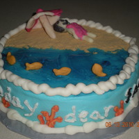Beach Cake Vanilla cake with buttercream frosting. Girl and umbrella are candy clay. Sand in graham cracker crumbs. Water is piping gel colored blue...