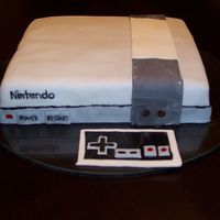 Original Nintendo This cake was for the groom at their bridal shower. It is a butter cake with chocolate frosting, covered in fondant. The lettering is hand...