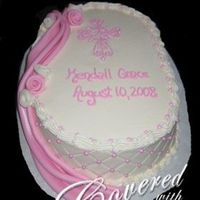 Baptism Cake With Drape And Cross Oval cake with buttercream quilting and fondant drape. Sugar pearls at cross sections.