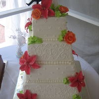 Square Cake With Flowers And Piping This was a 4 tier cake with fondant/gumpaste lilies, roses, and hydrangea blossoms in watermelon, tangerine and lime colors. The cake was...