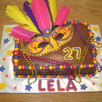 Mardi Gras Birthday Chocolate fudge cake with chocolate fudge buttercream icing. Fondant mask laid on a cardboard mask with feathers. Colorful Mardis gras...