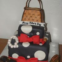 Gucci Purse And Shoe This was a RKT Gucci Purse with a Gucci shoe plus accessories on top of a black and white polka dot cake. The cake also came with 3 dozen...