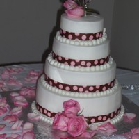 Elizabeth's Wedding Cake   Brown Ribbon with baby pink polka dots and pink roses. White/almond cake with buttercream icing.