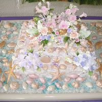 Luau 3 tiers cake with seashell made with white chocolate flavored with pina colada. sugar flowers and coconut flakes all around.