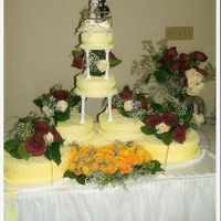 Our Wedding Cake Cake is lemon with lemon curd filling and lemon buttercream icing. Fresh flower arrangements on top of tiers and yellow roses between the...