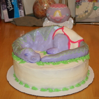 Dinosaur Baby Shower Cake Dinosaur made from rice krispies moulded into shape and covered in fondant. Cake covered in buttercream frosting.