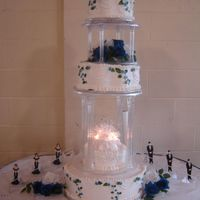 Wedding Cake With Royal Blue Roses  This was my first tall wedding cake with pillars. The swags are made from white chocolate roses lustered pearl and blue. I was very...