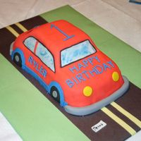 Car Birthday Cake this is covered in fondant and writing is in buttercream. For my cousins kids first birthday they loved it.