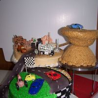 Cars on 3 tier cake stand/ royal icing buidings, rice krispi mountain. road from mountain is peanut butter (dirt) with cookie crumbs on cake...