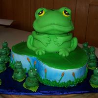 Frogs large frog's body is the doll mold pan, the head is the ball pan. cake is covered in fondant. the little frogs are cake balls dipped...