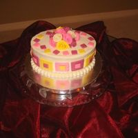 Squares And Roses   71/2 inch oval. White chocolate cake with lemon mousse filling and BC icing. Fondant accents.