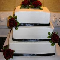 "Square Stacked 12"", 10"", 8"" squares. Buttercream icing w/black ribbon trim & silk red roses. Ribbon & Roses selected by the bride..."