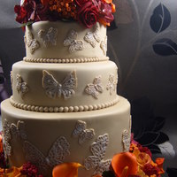Autumn Inspired Wedding Cake Autumn inspired cake with butterflies, sugar roses, calla lilies, chinese lanterns, berries and hydrangeas