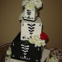 "White & Black Square Stacked  3"", 6"", 9"" sqaures styrofoams on top of a 12"" square cake, covered in fondant with white and black piping, all edged in..."