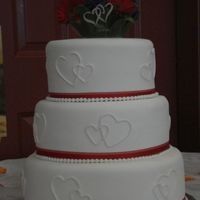 Zello Wedding Fondant covered with linked hearts made with fondant. Real ribbon and fondant pearl border.