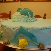 P8030744.jpg  This is a dolphin cake for a 10 year old girl who is a fanatic of dolphins. It is a two layer 16 inch cake top is white chocolate filling...