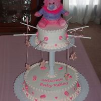 Pink Baby Mobile   Pink baby mobile. 12 inch round and 6 inch round cakes. All buttercream icing with fondant baby accents.