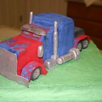 Optimus Prime carved cake to form truck, molded and hand painted with (petal dust) fondant accessories and truck