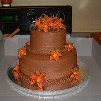 Chocolate Wedding Cake With Deep Orange Lily's This was my Course III Cake that I completed in class. I had a lot of fun with the flowers. I used a 10in and a 6in white cake with...