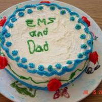 Ems & Dad This is a white cake with red roses around the side. The green stems connect each rose together. And then theres a blue outlining. My...