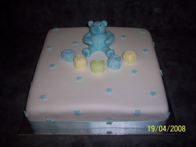 Teddy And Blocks Christening 12 inch square choc mud cake covered with fondant icing. Teddy, blocks and stars all fondant as well. Blocks spell out baby's name.
