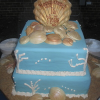 Sweet Sixteen Down By The Shore Cake is covered in fondant. Shells were made with white chocolate and dusted with luster dust. Sand is brown sugar