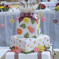 Daisy Wedding Cake All covered in Satin Ice Fondant with fondant decorations and flowers on covered floral wire.