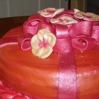 Orange W/ Pink Ribbon fudge round cake covered w/ orange mmf w/ mmf ribbon, all painted with orchid pink pearl luster.