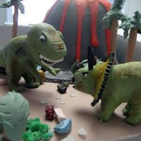 Dino Island Dinosaur cake for 5 year old's birthday. Vanilla cake with raspberry filling. Volcano is cake as well. Dinos are rice krispie treats...