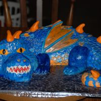 Dragon this was a very fun but time consuming cake. Each scale is hand cut and placed. The body is cake. The head and end of the tale is RCT.