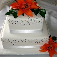 Tiger Lily Wedding Cake This cake has black and white piped dots on the sides in a random pattern with orange tiger lilies